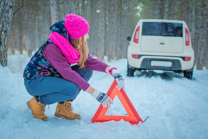 Woman setting up essential reflective triangle on road.